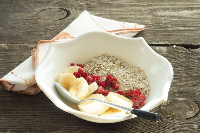 Oatmeal, banana and frozen strawberries in white bowl