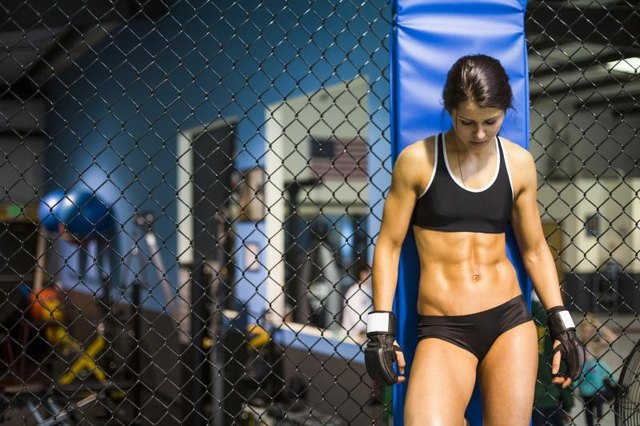 Female MMA fighter with well-defined abs.