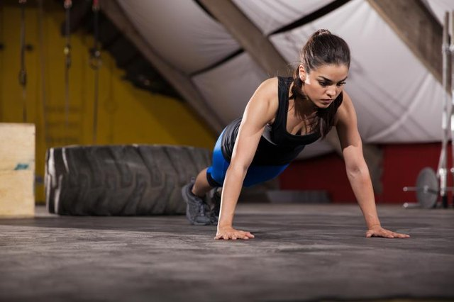 Athletic Latin woman doing push ups with extreme determination in a cross-training gym
