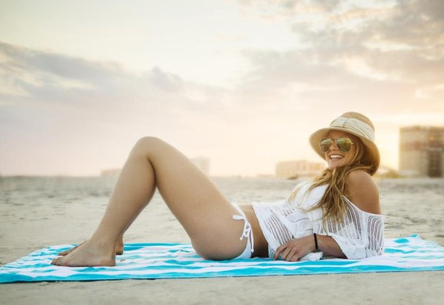 Young attractive woman laying out on a beach towel at Rockaway beach, Queens, New York City, New York