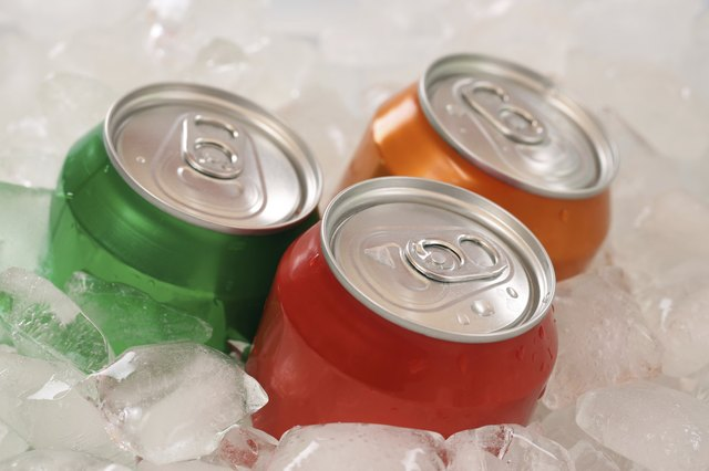 Cold cola and lemonade in cans on ice cubes