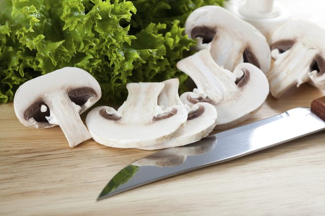 Mushrooms with knife on chopping board