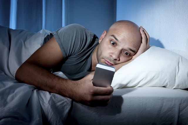 young cell phone addict man in bed using smartphone
