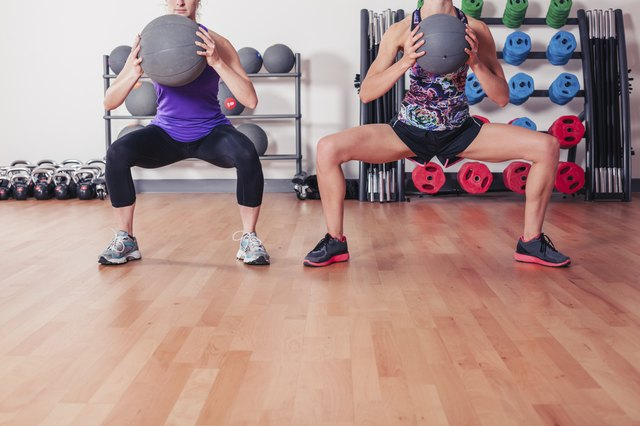 Two women with medicine balls