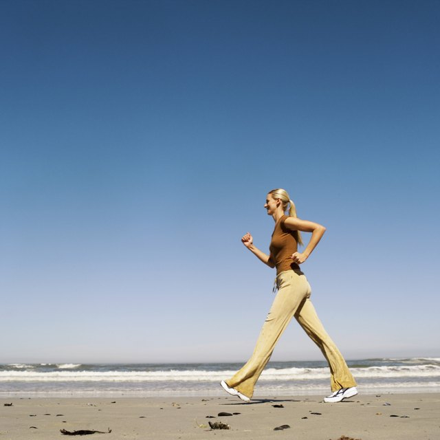 low angle view of a woman briskly walking on the beach