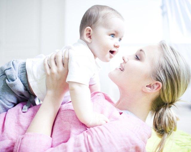 Teenage girl holding baby boy, close up