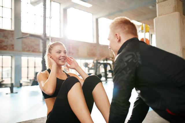 Indoor shot of a young woman doing sit-ups while a personal trainer holding her feet. Happy female  doing abs exercise with help from a man in gym.