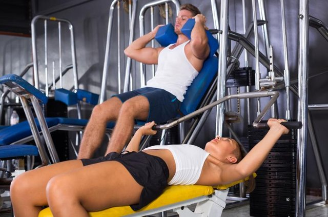 young sporty woman lying on back on bench and lifting weights in shoulder press machinery in gym