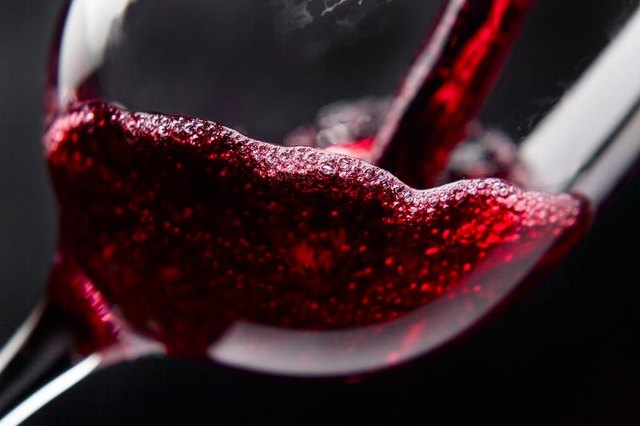Red wine in wineglass on black background
