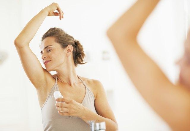 Woman enjoying freshness after applying roller deodorant on underarm