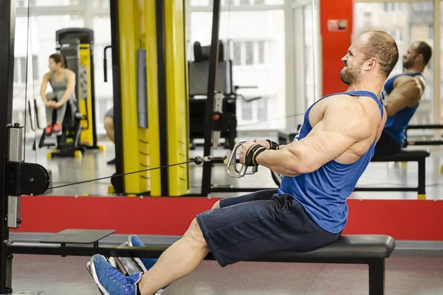Young male with strained face doing cable row exercises, guy building muscles