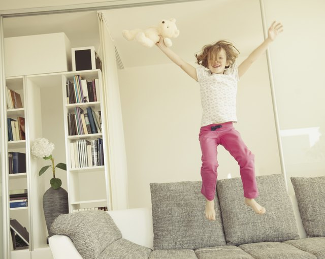 Young girl jumping on sofa