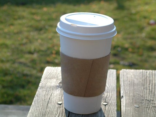 A lone coffee cup on a picnic table.