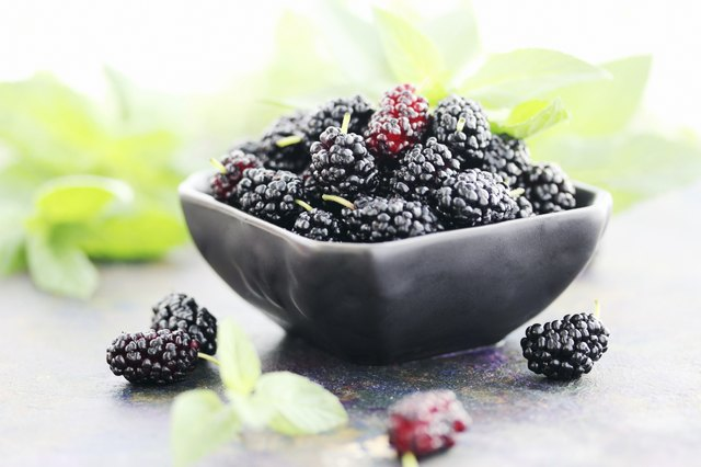 juicy mulberry on a black plate