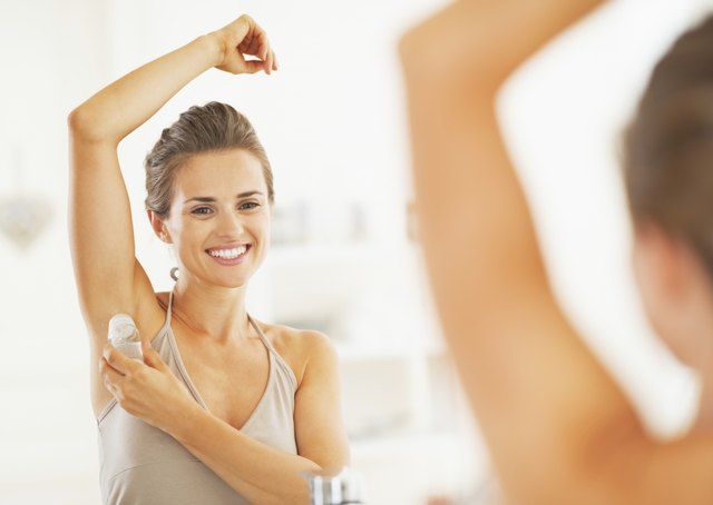 Smiling young woman applying roller deodorant on underarm in bathroom