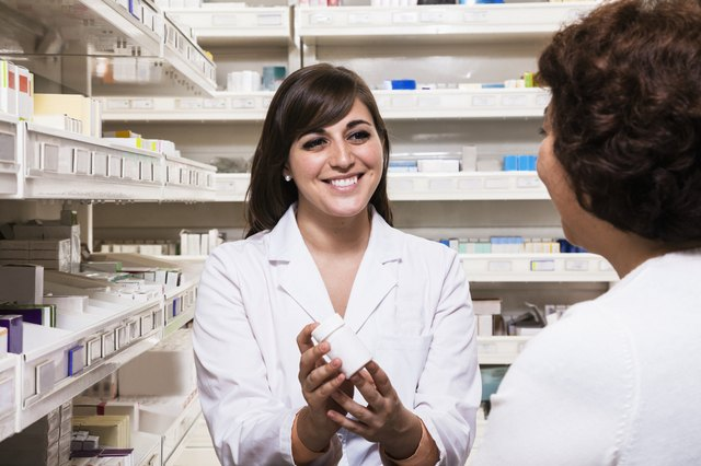 Smiling young pharmacist showing prescription medication to a customer