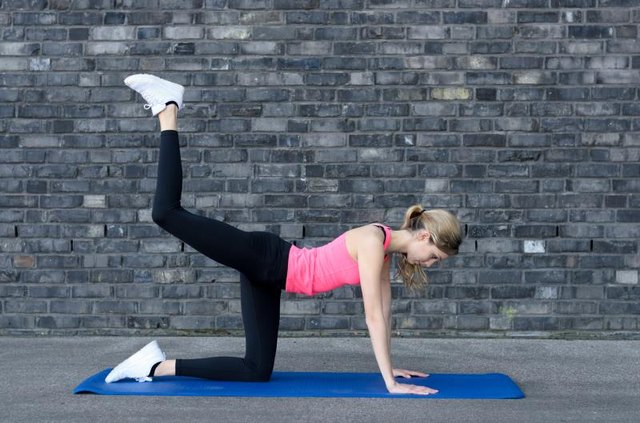 Fit woman in pink top and black tights strengthening her thigh muscles near grey brick wall