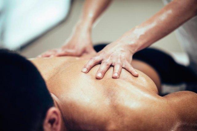 Sports massage. Massage therapist massaging stomach of a male athlete. Toned image