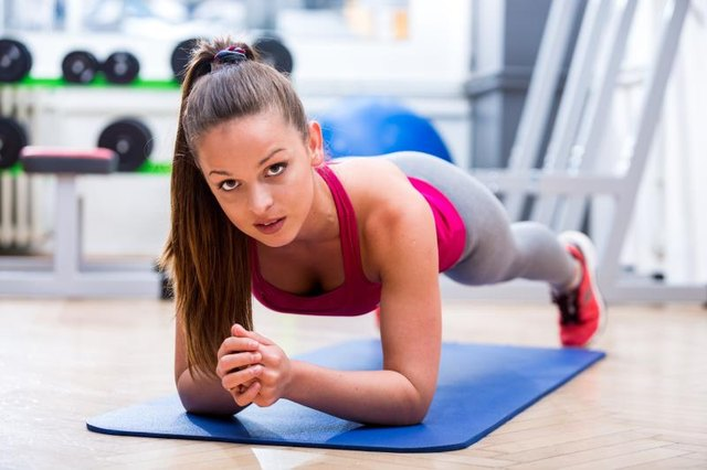 Cute, healthy, young athlete girl in sportswear while planking on a mat at the gym, expressing wellbeing and fitness.