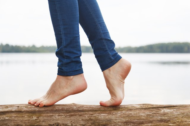 A woman's bare feet walking on a log near a lake