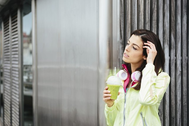 Fitness woman with detox smoothie cup