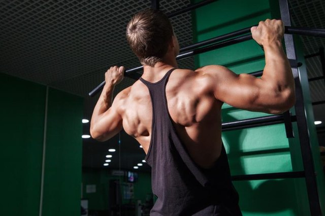 Back view of strong muscular sportsman doing pull ups in gym