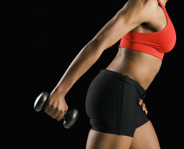 Side view if torso of African American young adult woman holding dumbbell outstretched.