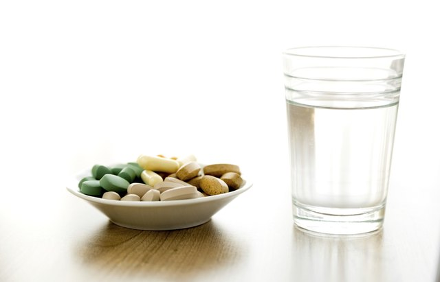 vitamin pills and a glass of water