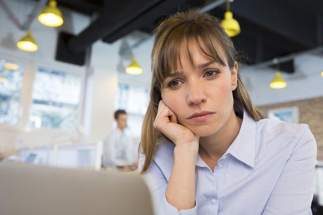 Depressed businesswoman in office behind her laptop