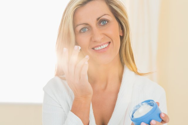 Pleased woman holding a jar of face cream in a hand and applying cream on her chick with the other h