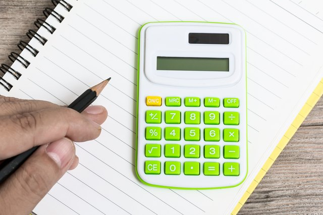 Hand Hold Pencil with Calculator Placed on Notebook