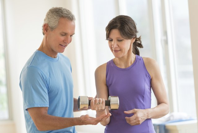Instructor Assisting Woman In Lifting Dumbbell