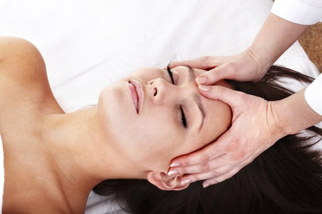 Young woman and beautician. Facial massage.