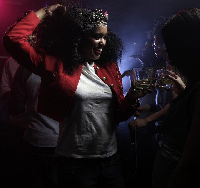 Two young women dancing in night club, one wearing crown