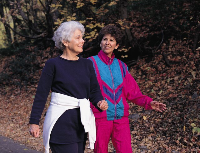 an elderly woman wearing black workout clothes walks with a middle-aged woman wearing red and blue workout clothes on a path covered with dead and fallen leaves