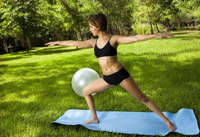 Latin woman outside on mat exercising.