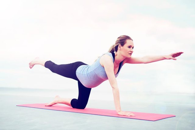 Young pregnant woman practicing pilates doing exercises to control and strengthen her muscles working out on a gym mat balancing outstretched on one knee