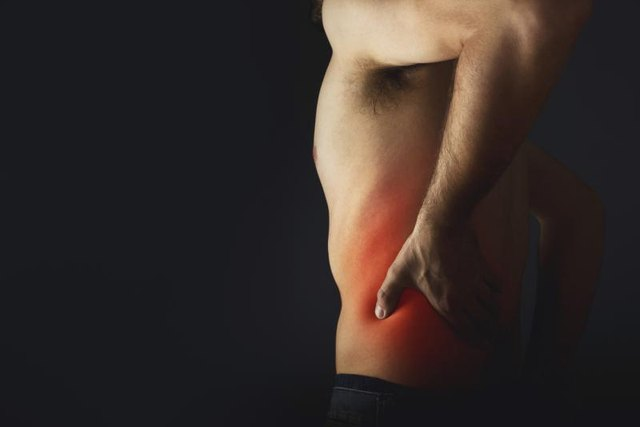 Backache. Pain in the lower back. Shirless man touching his back for the pain.