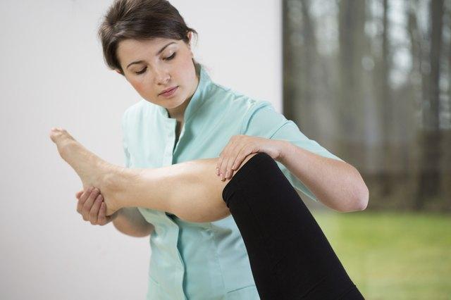 Physiotherapist flexing knee