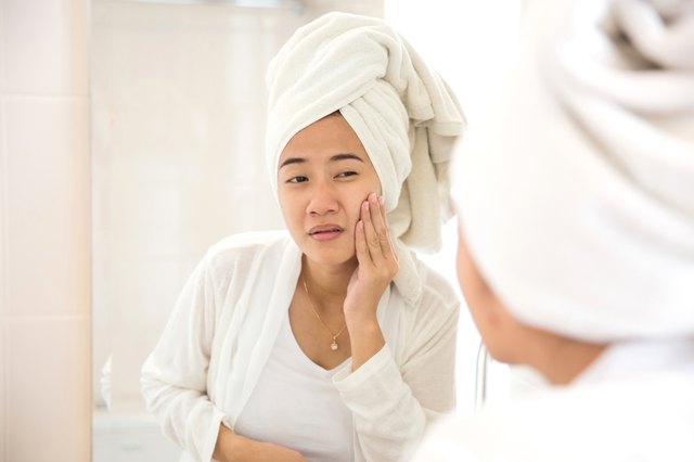 Young asian woman pressing her face, trying remove acne