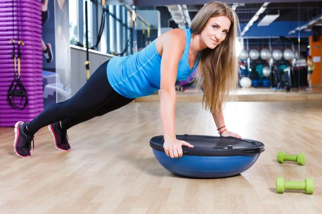 Young brunet athletic woman doing pushups on a bosu ball in the gym