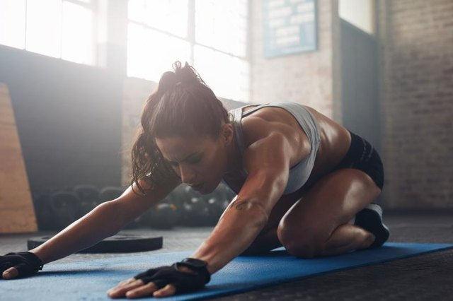 Shot of a young woman doing yoga on the gym floor. Muscular female doing stretching workout at health club.