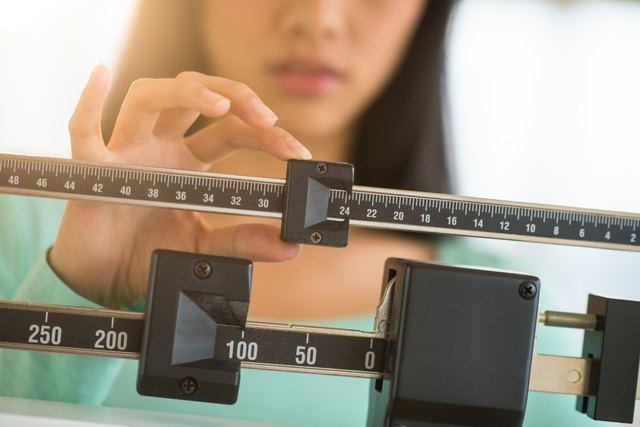 Midsection Of Woman Adjusting Weight Scale