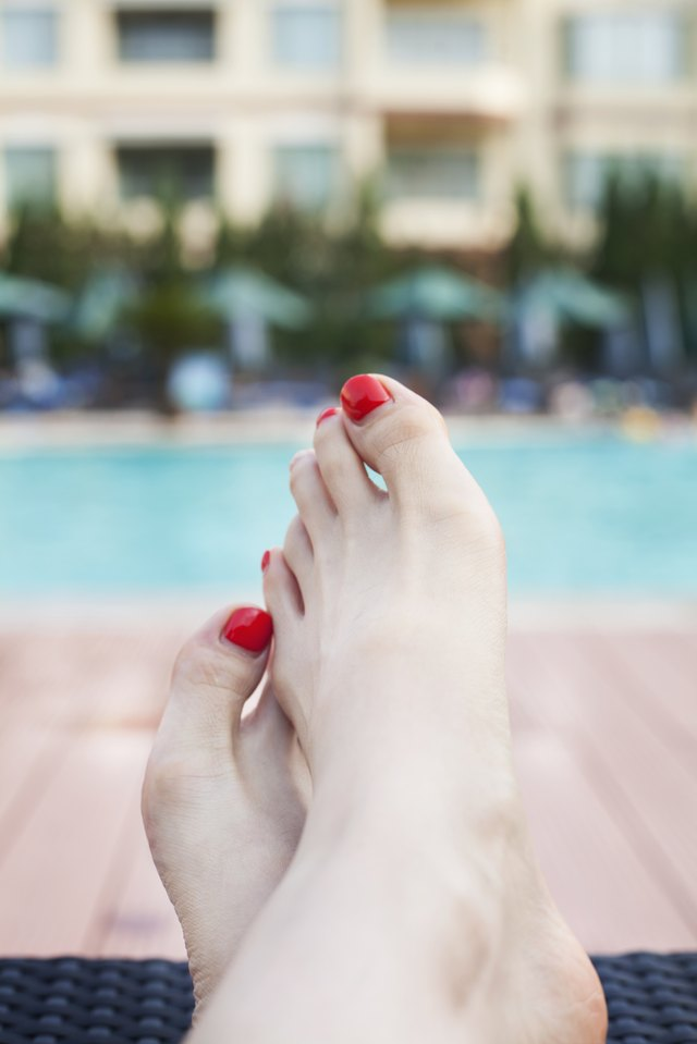 Close up of young woman's feet by the edge of the pool
