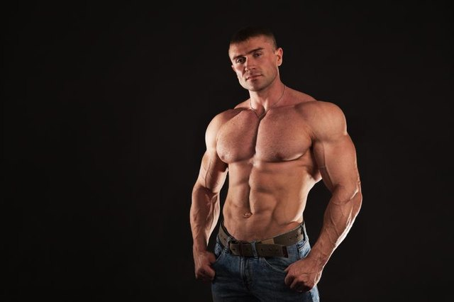 Big man with huge muscules. Bodybuilding and Healthy lifestyle concept, studio shot, dark background
