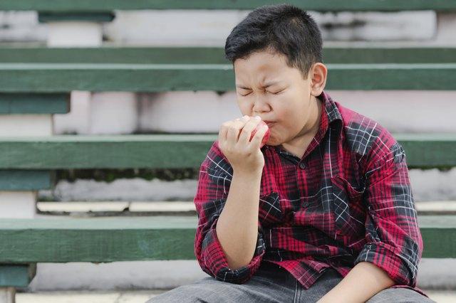 asian boy eating an apple