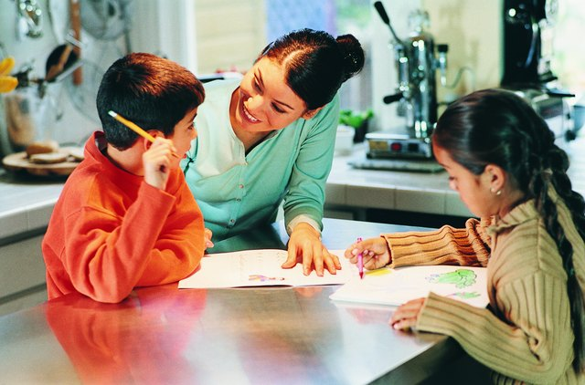 Mother Assisting Her Children With Homework in a Kitchen