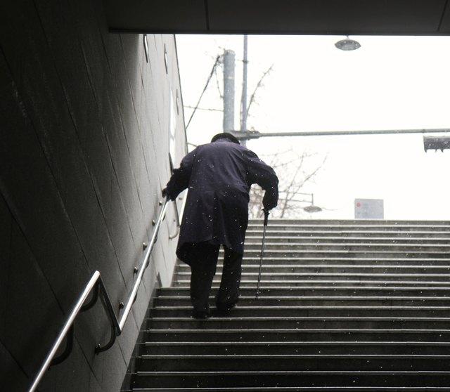 Elderly Man walking up a set of stairs during winter