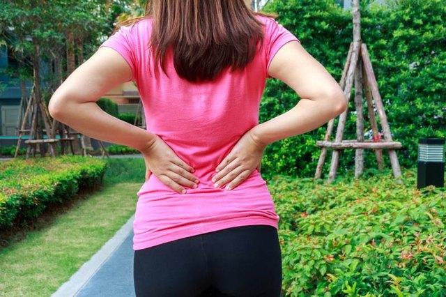 Female athlete lower back painful injury. Sporty woman backache and injury.
