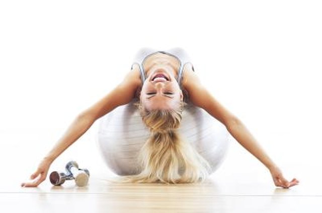 Woman lying on fitness ball